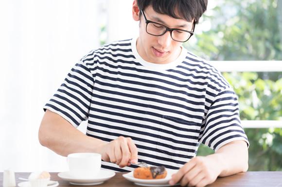 甘いものを食べる男性